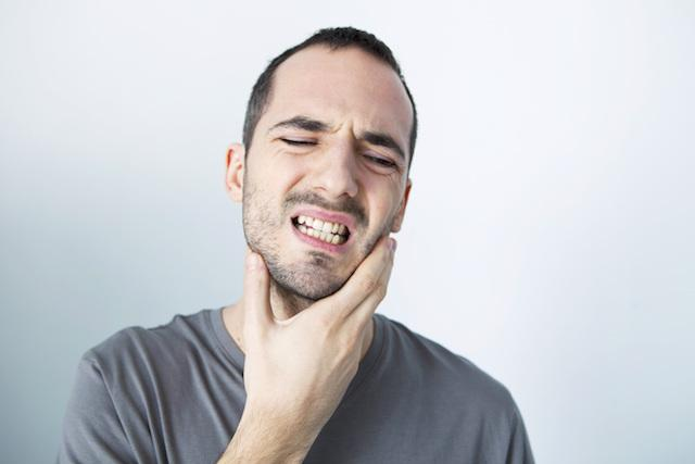 A Man Holds His Jaw | Root Canals Metairie LA