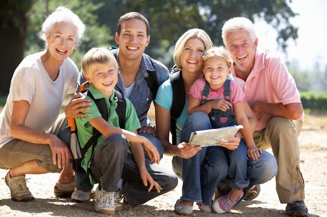 A Multi-Generation Family Smiles in front of a wooded area | Preventive Dentistry Metairie LA