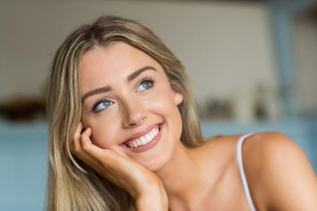 A woman smiles, looking off-camera | Invisalign Metairie LA