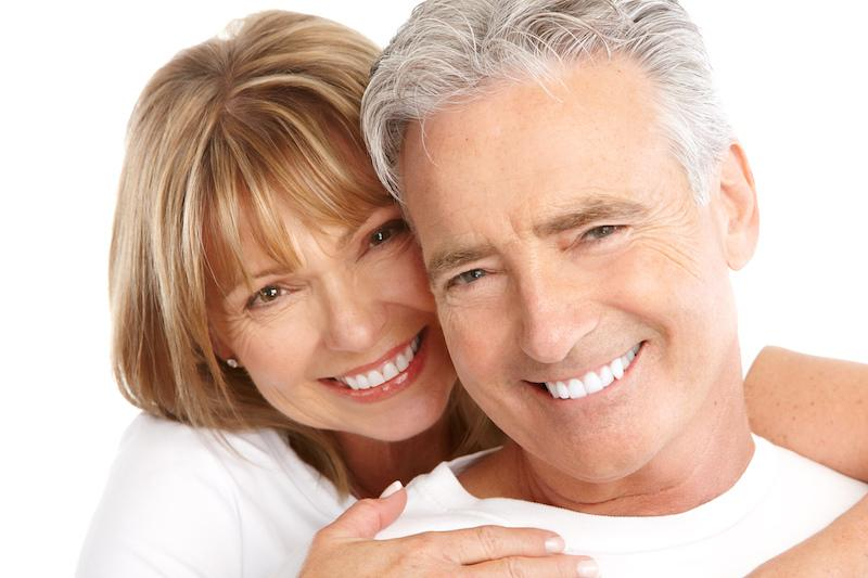 A Middle Aged Couple Smiles Over A White Background | Dental Implants Metairie LA