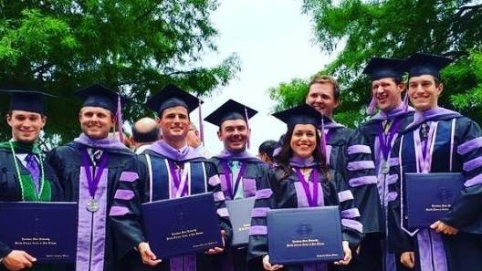 A group of graduates stands and smiles | Metairie Dentist | Oak Family Dental