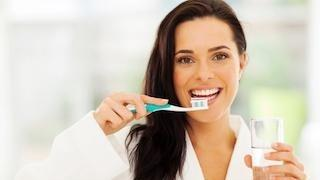A woman smiles while she brushing her teeth | metairie la dentist