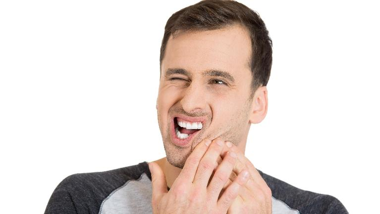 a man puts his hand to his jaw | Metairie LA TMJ Treatment