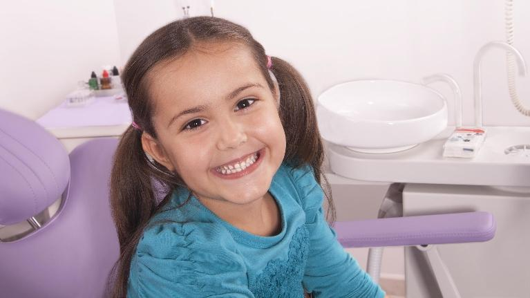 a girl smiles in the dental chair | pediatric dentist metairie