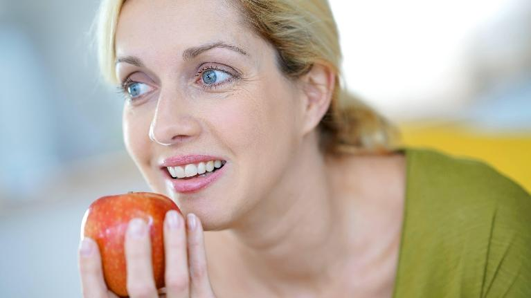A woman hesitates to bite into an apple | root canals Metairie, LA