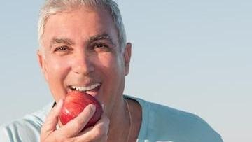 man holding apple | dentures metairie la