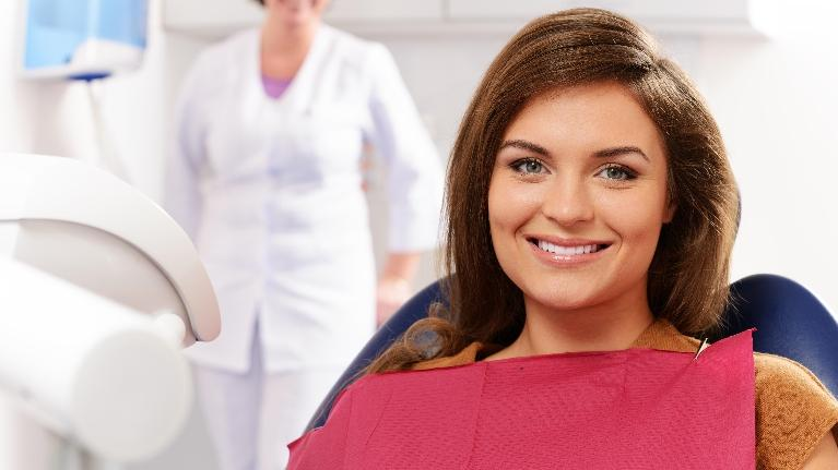 a woman smiles in the dental chair | dental crowns metairie la
