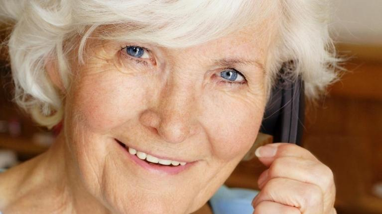 A woman smiles as she's on the phone | Dentures Metairie LA