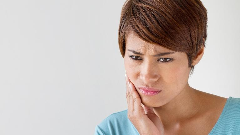 A woman holds her hand to her jaw | extractions metairie LA