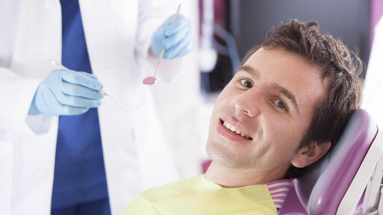 A man smiles in the dental chair | gum disease metairie