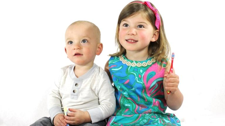 Two children smile in front of a white backdrop | children's dentist metairie la