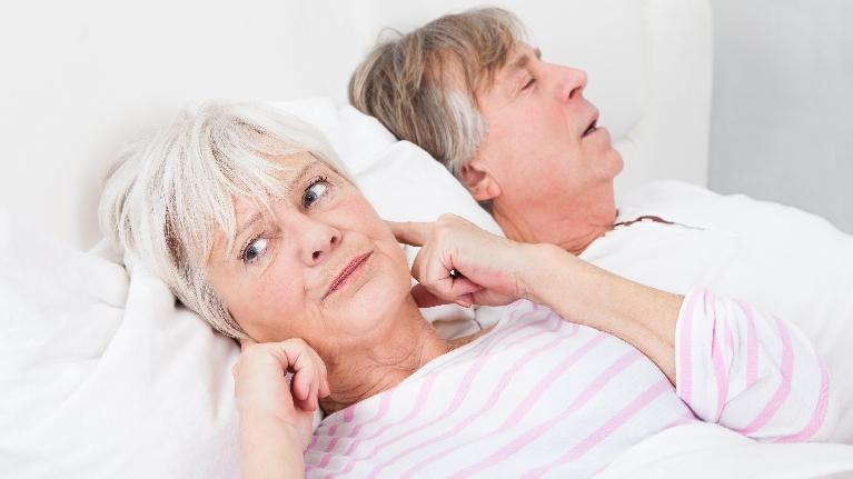 A woman plugs her ears next to her sleeping husband | Sleep Apnea Treatment Metairie