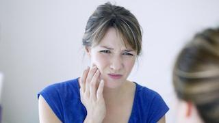 A woman holds her jaw, looking at herself in the mirror | root canals Metairie la