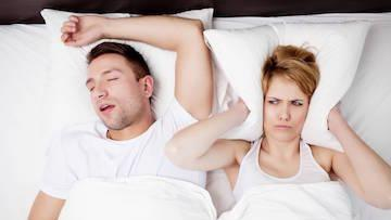 A couple lays in bed | Sleep Apnea Metairie LA