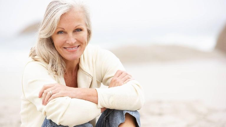 A woman sits and smiles on the beach | Metairie LA root canals