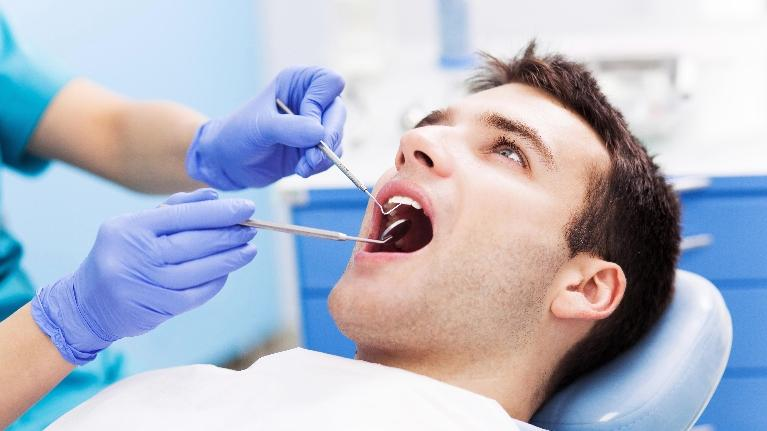 A man gets his teeth examined | dentist in metairie, LA