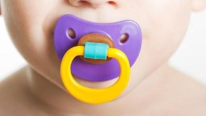 A close up image of a child with a pacifier in their mouth | Pediatric Dentist Metairie LA